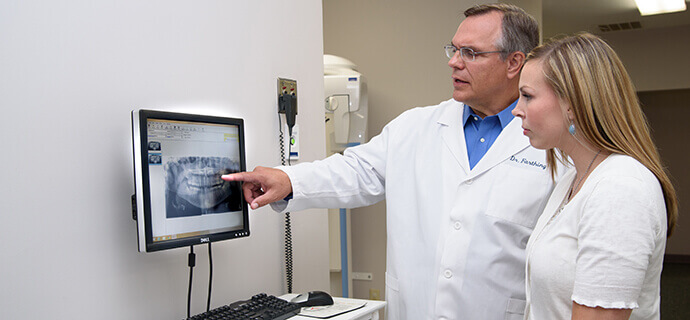 dentist showing patient x-ray