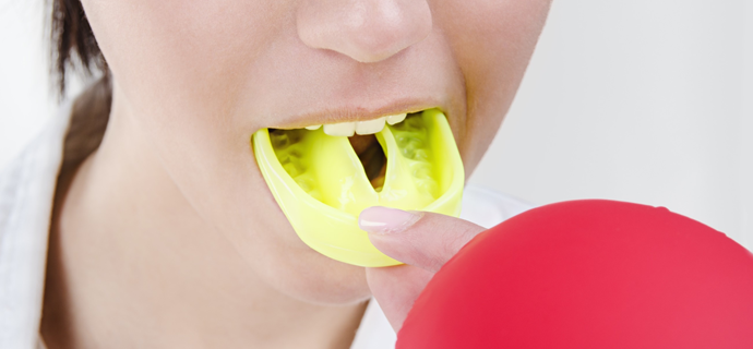 Woman placing athletic mouthguard