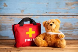 teddy bear sitting next to a first aid kit