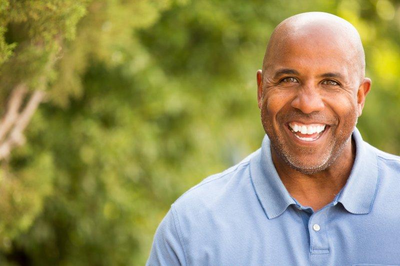older man smiling nice teeth from implant dentures