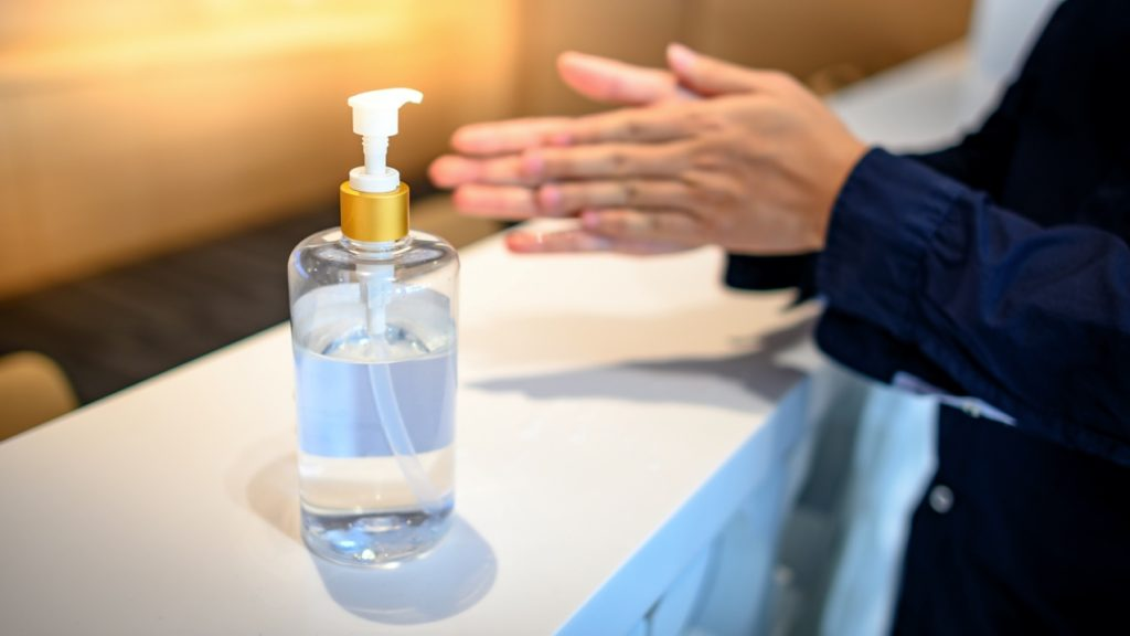 Patient using hand sanitizer at dentist