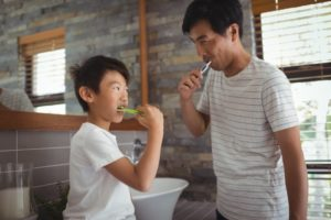 a parent brushing their teeth with their child